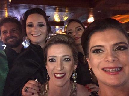 A imagem pode conter: 5 pessoas, pessoas sorrindo, noite, área interna e close-up