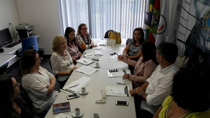 A imagem pode conter: 4 pessoas, pessoas sentadas, tabela e área interna