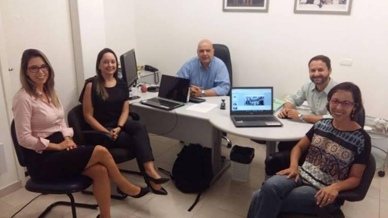 A imagem pode conter: 5 pessoas, pessoas sorrindo, pessoas sentadas, tela, escritório e área interna