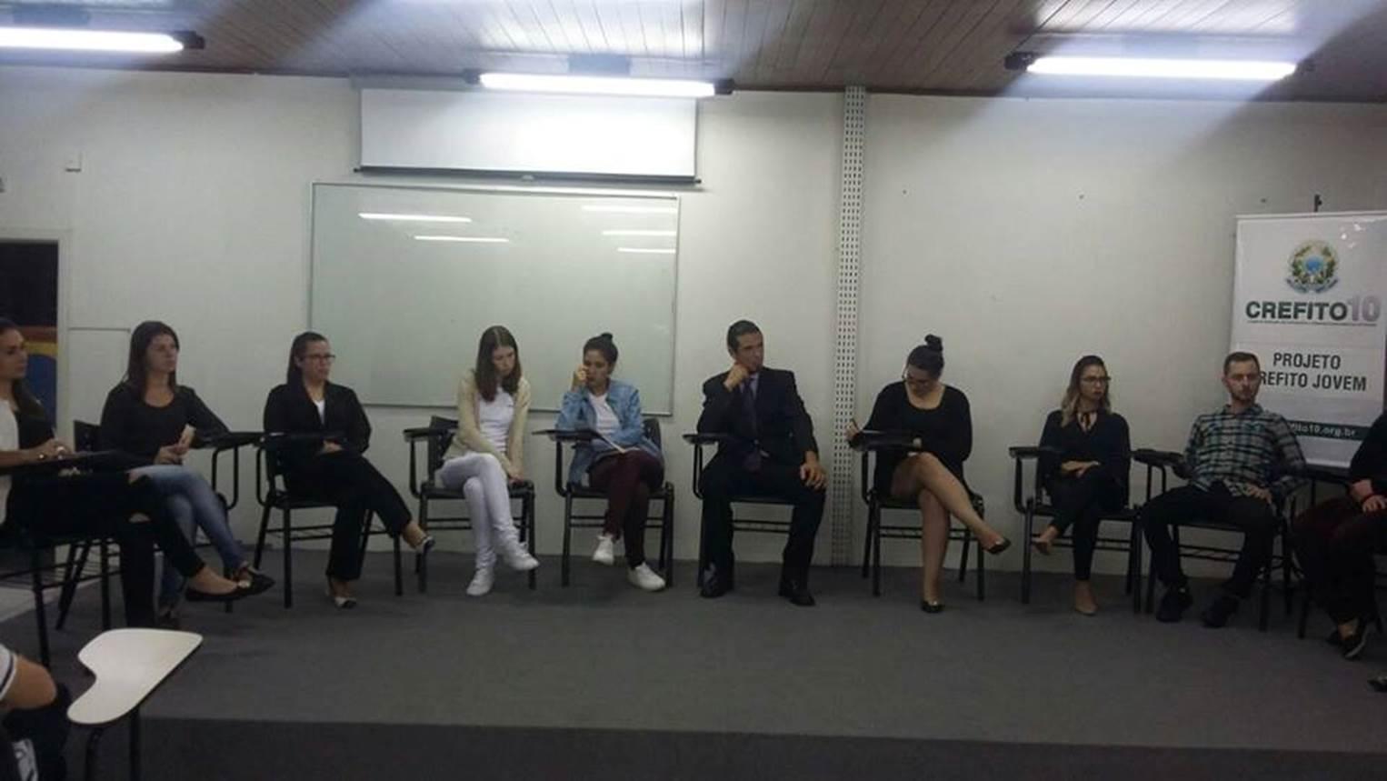 A imagem pode conter: 3 pessoas, pessoas sentadas e área interna