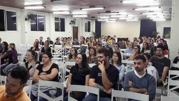 A imagem pode conter: 14 pessoas, pessoas sentadas e área interna