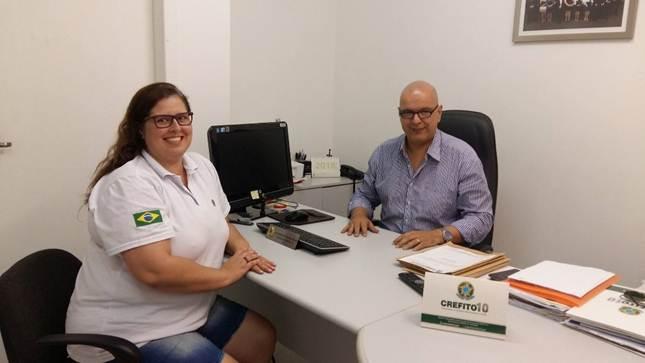 A imagem pode conter: 2 pessoas, pessoas sorrindo, pessoas sentadas, tela, escritório e área interna
