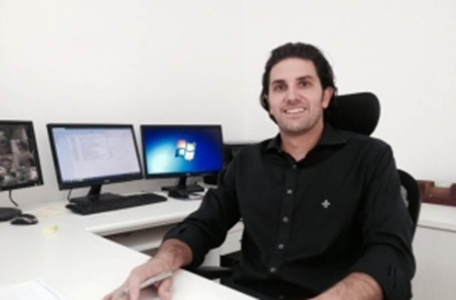 A imagem pode conter: 1 pessoa, sorrindo, sentado, tela, escritório e área interna