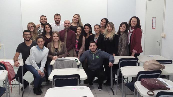 A imagem pode conter: 17 pessoas, pessoas sorrindo, pessoas sentadas e área interna